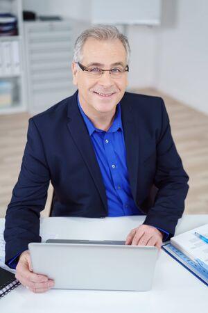 hombre escribiendo: hombre de negocios de mediana edad que trabaja en un ordenador portátil en su escritorio en la oficina mirando a sonreír a la cámara, vista de cerca