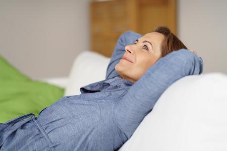 Feliz mujer de mediana edad se relaja en su casa de descanso en un cómodo sofá con las manos detrás de la cabeza mirando hacia arriba con una sonrisa soñadora del placer