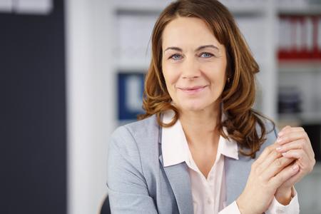 Mittleren Alters Geschäftsfrau mit einem natürlichen freundlichen Lächeln sitzt schaut in die Kamera mit ihren gefalteten Händen vor ihr