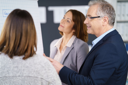 Three adult business people discussing metrics or marketing strategy while standing in front of chart at office