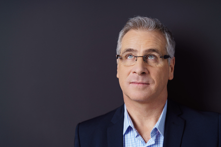 coo: Thoughtful attractive middle aged businessman wearing glasses standing looking up into the air, close up head and shoulders with copy space Stock Photo