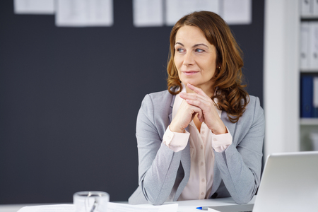 Thoughtful businesswoman sitting at her desk in the office looking to the side watching something, with copy space Foto de archivo