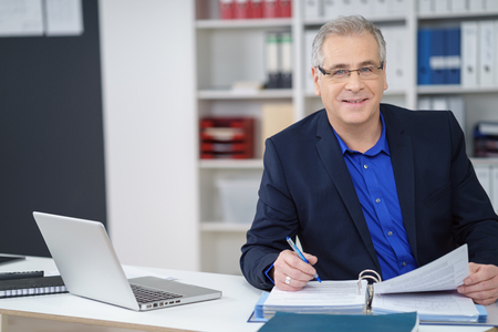 Business executive wearing glasses sitting working at his desk on paperwork in a binder looking at the camera with a smile Stockfoto