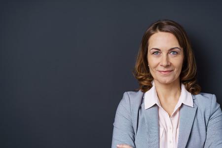 Attraktive mittleren Alters Geschäftsfrau mit einem freundlichen Lächeln zuversichtlich mit verschränkten Armen vor einem dunklen Hintergrund mit Kopie Raum aufwirft