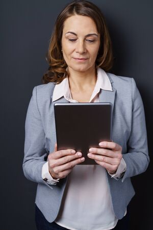 downcast: Businesswoman standing reading a handheld tablet computer with downcast eyes and a quiet smile, upper body close up Stock Photo