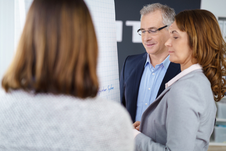 senior women: Three adult workers discussing business or marketing strategy while standing in front of chart at office Stock Photo