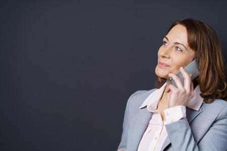 Geamuseerd vrouw luisteren naar een mobiel telefoongesprek te zoeken in de lucht met een leuke glimlach, met kop en schouders boven een donkere achtergrond met kopie ruimte