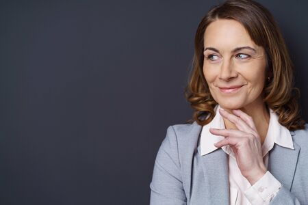 donne eleganti: Smiling businesswoman with a thoughtful expression standing with her hand to her chin looking to the side to blank copy space on a dark background Archivio Fotografico