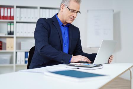 escribiendo: Hombre de negocios sentado en una mesa en la oficina de la navegación por Internet en un ordenador portátil con una expresión absorta, bajo ángulo de vista