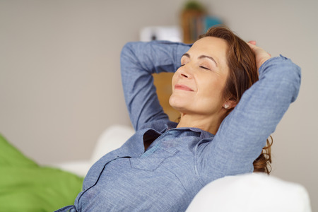 calm woman: Successful businesswoman relaxing at home on a sofa with her hands behind her head, eyes closed and smile of pleasure on her face Stock Photo