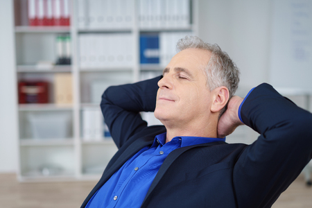 male hand: Stressed businessman taking time out relaxing in his char at the office with his ands behind his head and eyes closed Stock Photo