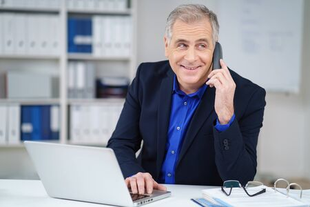 smiling businessman: Businessman chatting on a phone in the office looking to the side with a smile as he listens to the call, natural pose