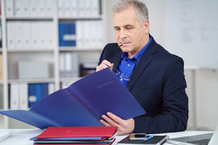 business report: Thoughtful manager reading through a report or CV in a blue folder with a look of concentration as he sits at his desk in the office