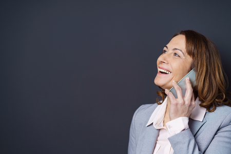 reacting: Businesswoman laughing as she chats on a mobile phone reacting with pleasure to the conversation, head and shoulders with copy space