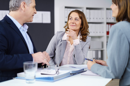 managerial: Three managerial business colleagues in a meeting sitting grouped around a table having a serious discussion, focus to an attractive middle-aged woman Stock Photo