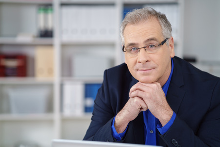 chin on hands: Thoughtful businessman wearing glasses sitting at his desk in the office resting his chin on his hands looking at the camera