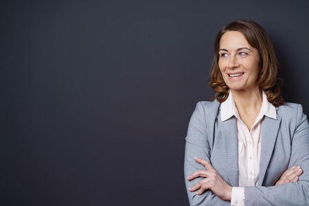 Confident middle-aged businesswoman standing with folded arms smiling with pleasure and amusement as she looks towards blank copy space on a dark background