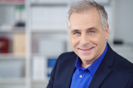 looking directly at camera: Attractive middle-aged businessman with a friendly smile looking directly at the camera, head and shoulders in the office