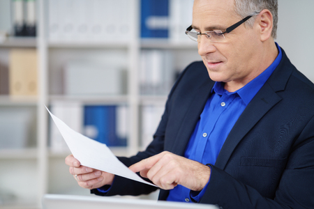 hombre escribiendo: Businessman wearing glasses sitting at his desk in the office carefully reading a paper document