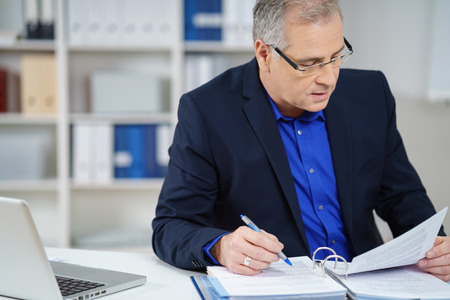 business report: Businessman compiling a business report as he sits at his desk making notes and reading information in a binder