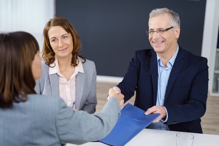 business transaction: Three happy executives closing an important business transaction or negotiation and exchanging documents while sitting in office with copy space
