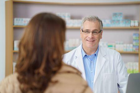 Atractiva farmacéutico de sexo masculino de mediana edad permanente de audición a una paciente en la farmacia, por encima del hombro vista de su cara