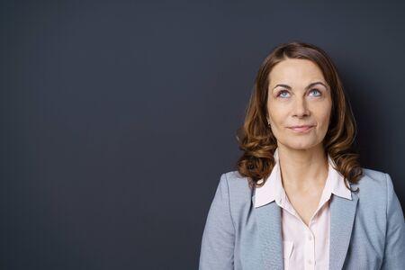 donne eleganti: Donna di affari premurosa guardando in aria con una espressione pensosa come lei si trova su uno sfondo scuro, la testa e le spalle con lo spazio della copia