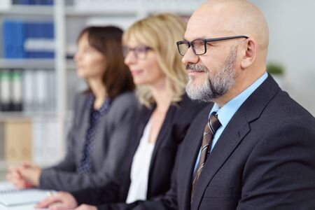 entrepeneur: Three business executives in a management meeting sitting together at a table listening to a presentation with focus to a bald middle-aged man in the foreground with a quiet smile