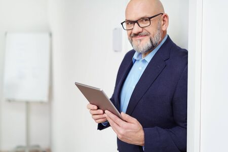 bald head: Single handsome mature bearded man with eyeglasses and bald head holding tablet computer while leaning against wall with copy space