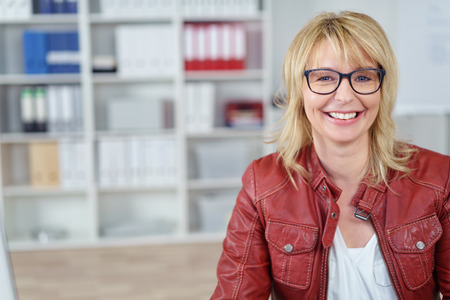 Smiling single blond business woman in red leather jacket and eyeglasses at small office with copy space over bookshelf area