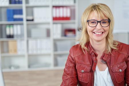 Glimlachende blonde zakenvrouw in rode leren jas en bril op kleine kantoor met kopie ruimte over boekenplank gebied Stockfoto