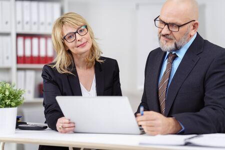executive women: Serious male and female executives with calm expression working together on laptop computer behind white table with little plant nearby in office