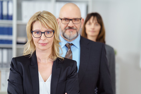 in a row: Successful business team with diverse professionals with a man and two women and focus to a team leader or manageress in the foreground
