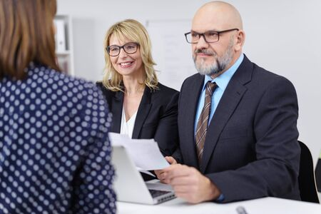 one on one meeting: A middle-aged businessman and woman wearing glasses sitting in a meeting listening to a female colleague, one smiling, one serious Stock Photo