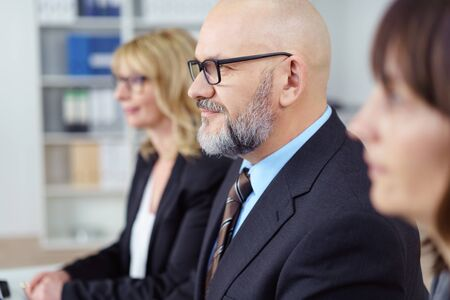 serious businessman: Attractive senior businessman with a shaved head and glasses seated in a meeting listening with a serious expression, close up selective focus between two women Stock Photo