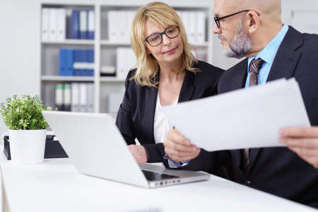 economists: Handsome bearded business man with necktie, suit and eyeglasses showing woman something on papers next to computer