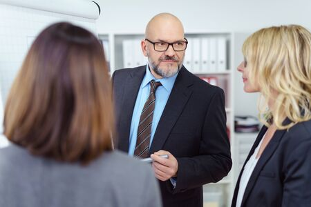 balding: Senior businesspeople in a meeting standing grouped around a flip chart having a serious discussion, focus to a balding man in glasses