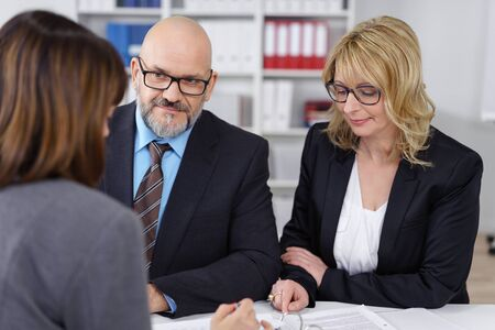 management team: Middle-aged management team in a meeting with a serious businessman and woman listening to a female colleague speaking with thoughtful expressions Stock Photo