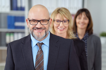 Smiling friendly male business executive wearing glasses standing in the foreground of his successful team of two female co-workers Stock Photo