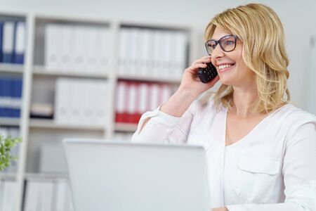 mujeres pensando: Attractive blond businesswoman wearing eyeglasses taking a call on her mobile with a smile as she sits working on a laptop in the office