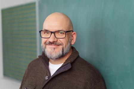 眼鏡をかけて教室で空の黒板の横に立っている中年男性教師にひげを生やした笑みを浮かべて、頭と肩を閉じる 写真素材