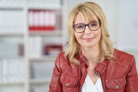 single shelf: Grinning single mature woman in red leather jacket, blond hair and eyeglasses with cheerful expression in office with shelf in background Stock Photo