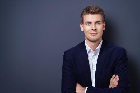 Fiducioso bel giovane uomo d'affari in una giacca elegante in piedi con le braccia conserte sorridendo alla telecamera su uno sfondo scuro con spazio di copia