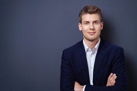 Confident handsome young businessman in a stylish jacket standing with folded arms smiling at the camera over a dark background with copy space