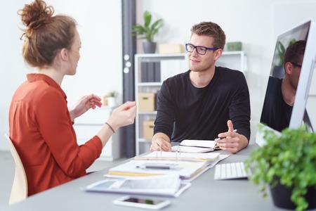 Jonge zakenman en vrouw in een vergadering met een geanimeerde discussie als ze zitten samen op een bureau, richten zich op de jonge man dragen van een bril Stockfoto