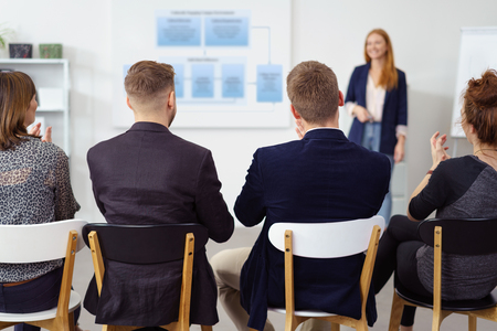 view from behind: Attentive group of business colleagues sitting in a meeting listening to a presentation given by an attractive redhead female colleague, view from behind their backs