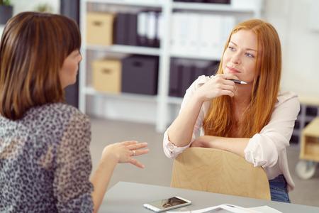 pessoas: Mulher de negócios dois tendo uma reunião informal com uma sessão relaxante em uma cadeira revertida ouvindo seu colega com uma expressão pensativa