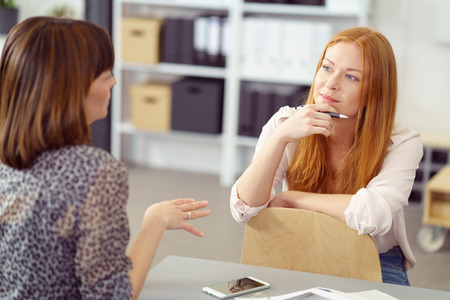 Two businesswoman having an informal meeting with one sitting relaxing on a reversed chair listening to her colleague with a pensive expression. Stock Photo