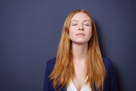 tilted: Attractive young woman enjoying a quiet moment standing meditating with her eyes closed and head tilted back, dark studio background with copy space Stock Photo