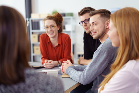 Five young business partners in a meeting sitting listening with a smile to a woman with her back to the camera